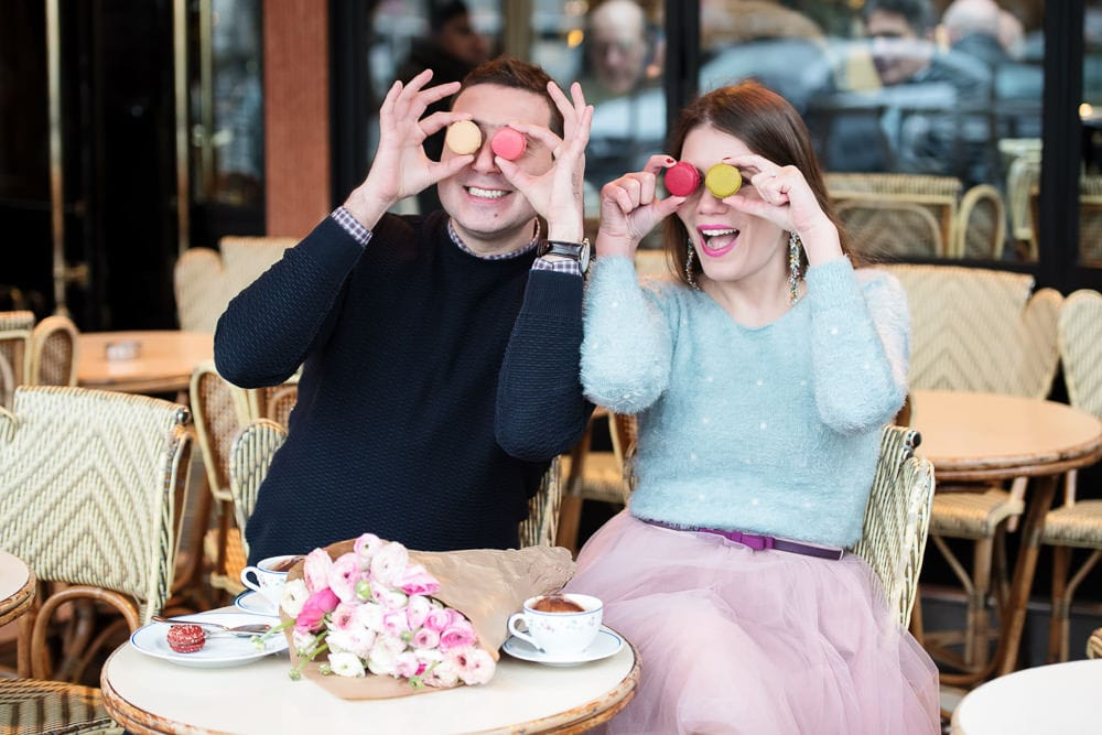Couple having fun with colorful macarons in a parisian café