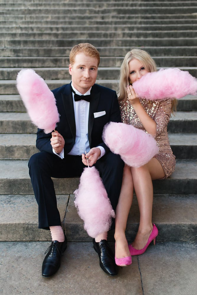 Stylish couple posing for engagement photos with pink cotton candy