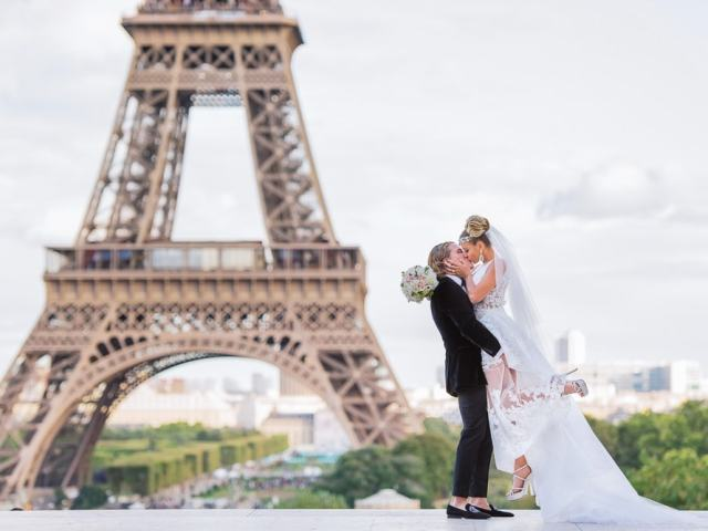 Bride kissing her groom while he is lifting her in the air in front of the Eiffel Tower