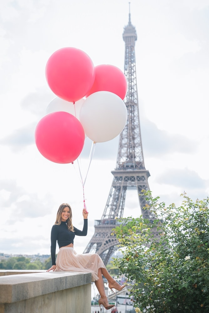 Cute girl dressed in black top and pink tutu dress with red and white balloons smiling in Paris