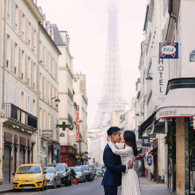 Girl kissing boy in a street overlooking the Eiffel Tower
