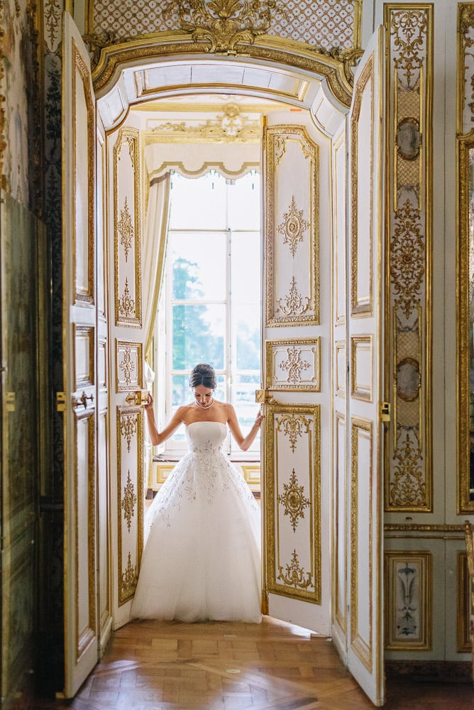 eloping in paris bride in haute couture dior dress opening doors at the chateau de chantilly