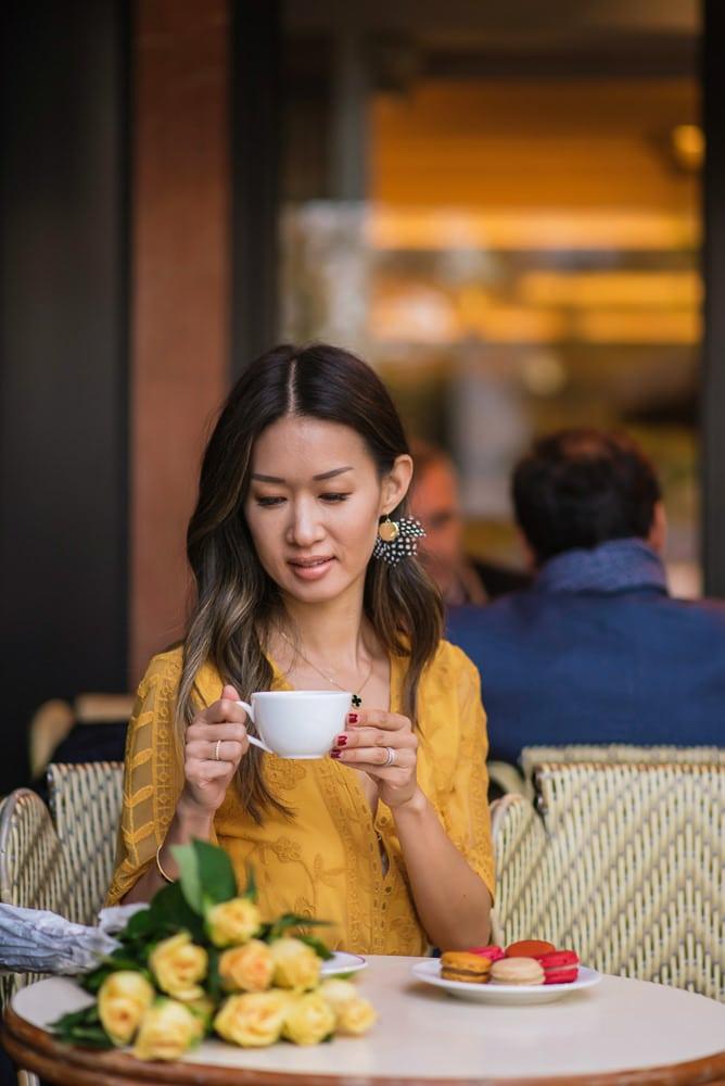 beautiful girl dressed in yellow dress having a coffee in paris