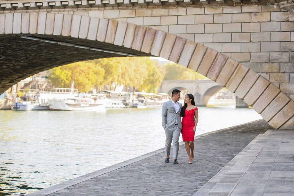 Elegant couple walking along the Seine river under the Louis Philippe bridge