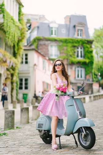 Beautiful girl sitting on a Vespa in the streets of Montpartre Paris