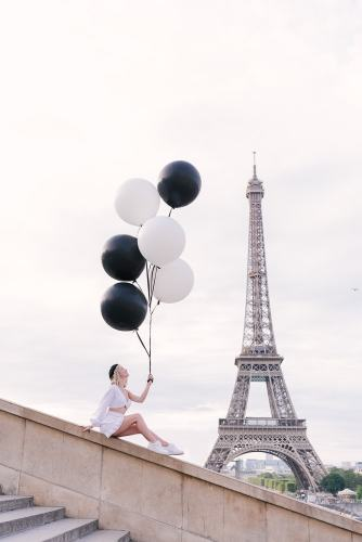 Girl with black and white balloons posing at Eiffel Tower
