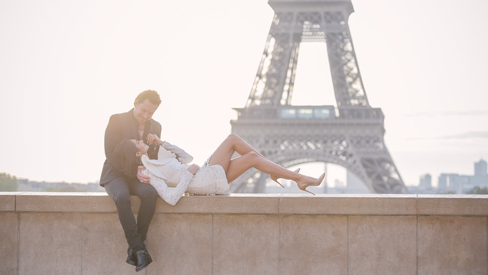 Elegantly dressed couple posing for romantic photos in front of the Eiffel Tower