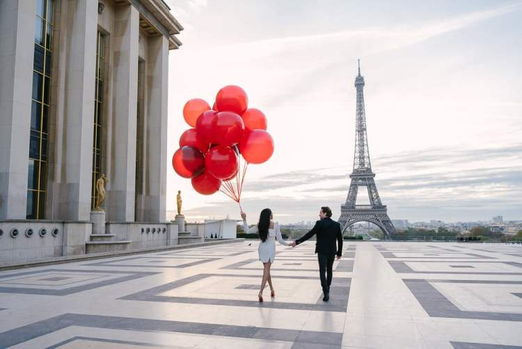 Trocadero Paris at sunrise - Elegant couple walking with red balloons towards the Eiffel Tower