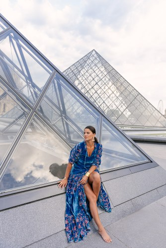 Stylish girl posing in front of the Louvre Pyramid in Paris