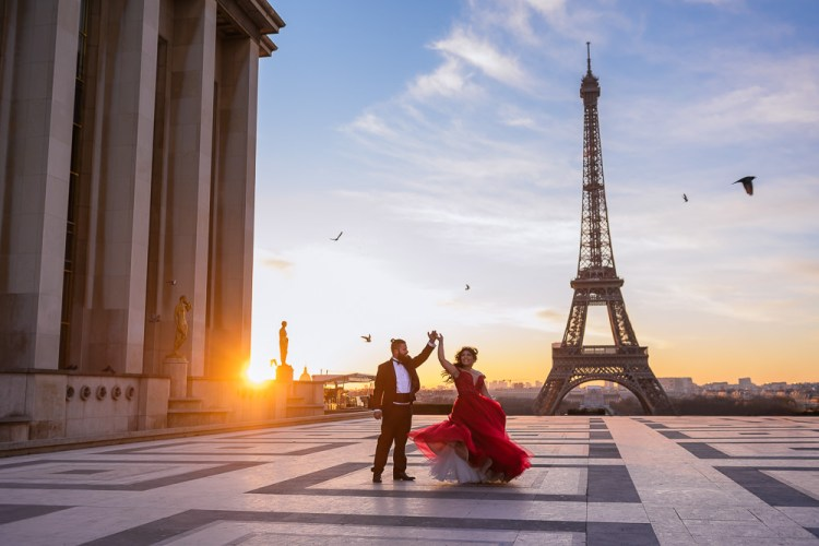 Beautiful couple dancing in front of the Eiffel Tower at sunrise