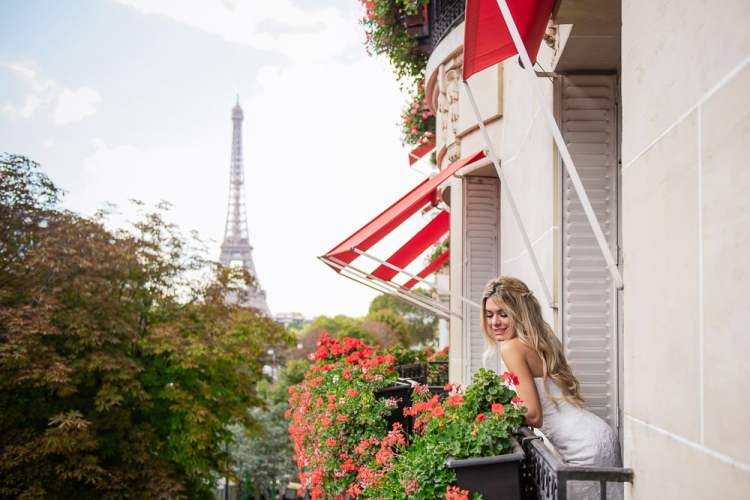 Bride posing for pictures during getting ready moments on her balcony at Plaza Athénée