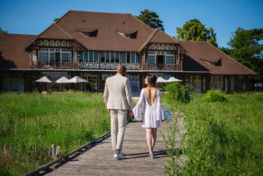 Newly married couple walk into their wedding venue in Paris Le Pavillon des etangs