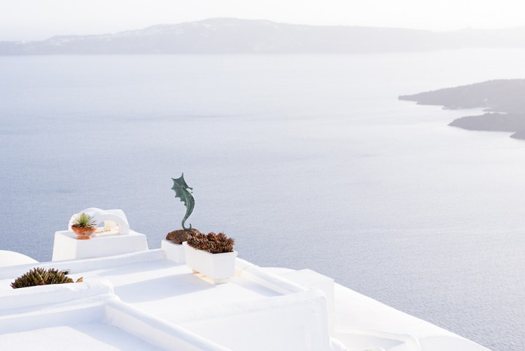 Santorini postcard with white rooftops and sea water