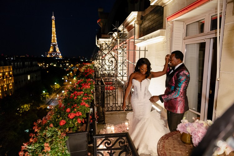 Bride and groom celebrating marriage on a Parisian balcony with Eiffel Tower in the background