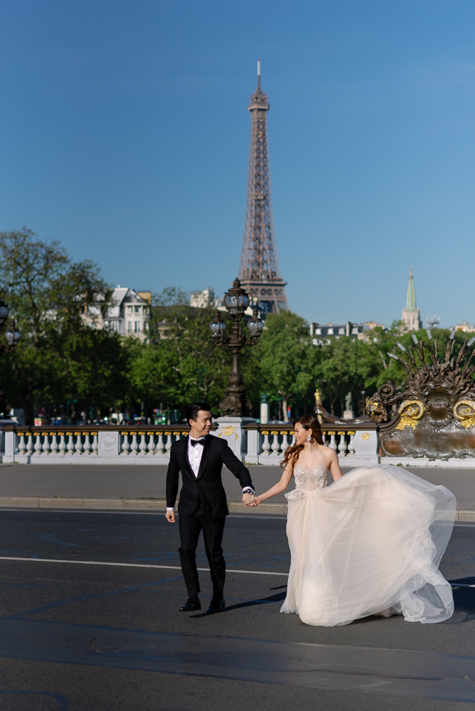 Bride and groom crossing the street in one of the best eiffel tower spots in Paris