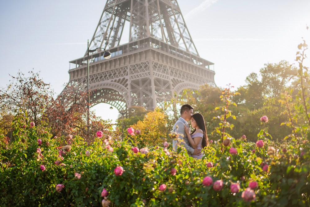 Couple kissing in the sunshine surrounded by beautiful roses and the Eiffel Tower