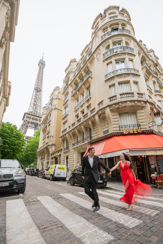 Couple running across the street near the Eiffel Tower