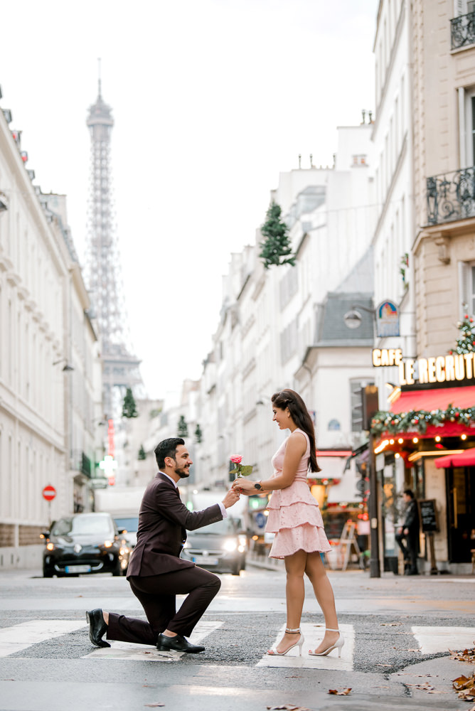 Gentleman on one knee offering rose to his fiancée
