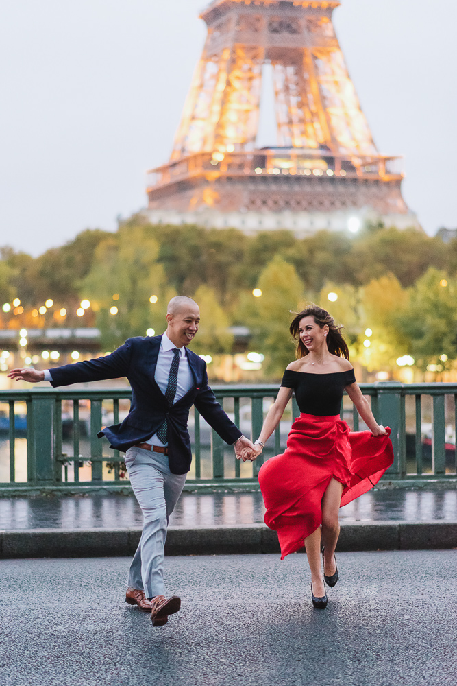 Happy couple running across the street in Paris in one of the most beautiful spots with eiffel tower view