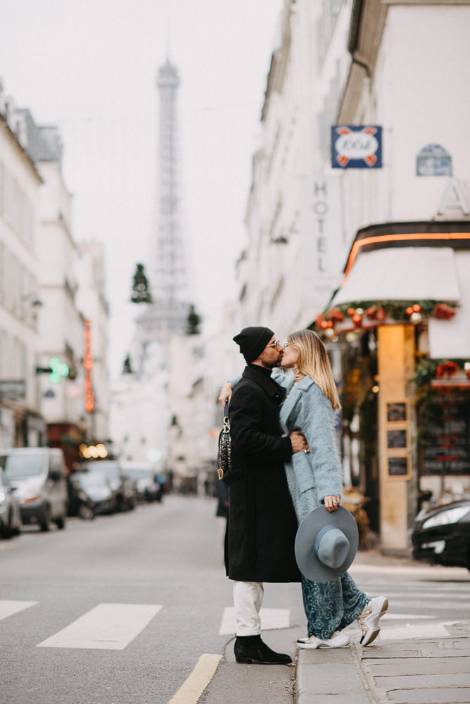 Young couple kissing in the streets of Paris near the Eiffel Tower