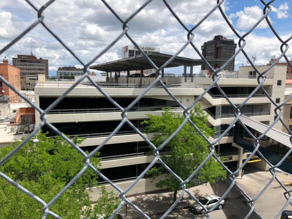 Photo of parking garage behind chain link fence.