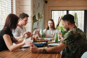 Side view picture of a group of friends praying over dinner table