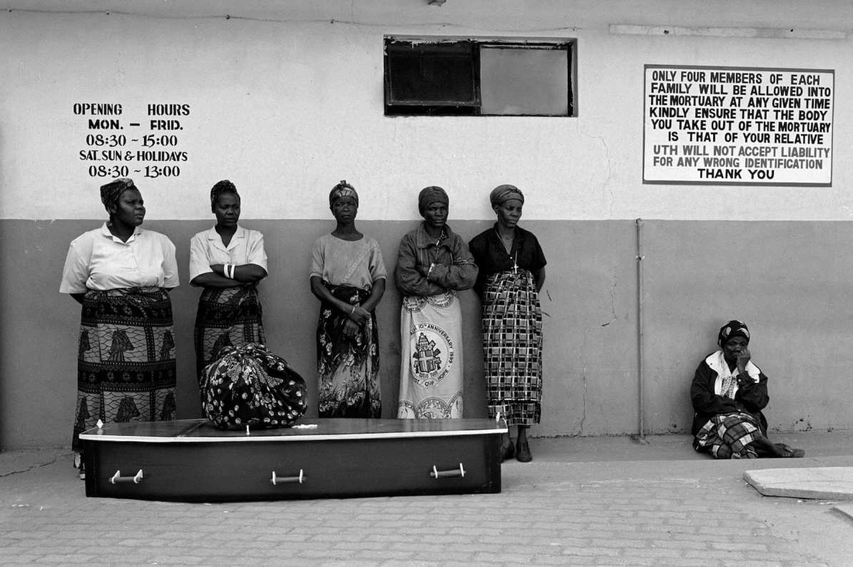 P61. Members of the family of the deceased, Joyce Tembo, wait in line at the mortuary in Lusaka, Zambia to pick up her body after it had been prepared for burial by family members. She passed away on Saturday and is being buried on Tuesday, one of the busiest days of the week for funerals in Lusaka. A sign on the wall warns of misidentification, a problem when so many bodies are being prepared and picked-up on one day.