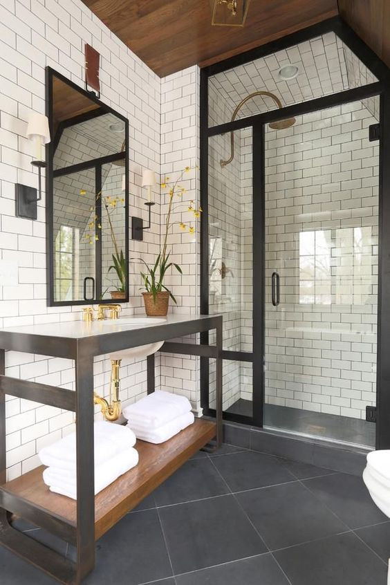 Designed by Summer Thornton, this black and white bath has many familiar elements associated with industrial design--a metal framed washstand, a shower door that resembles a factory window and simple white rectangular tile.