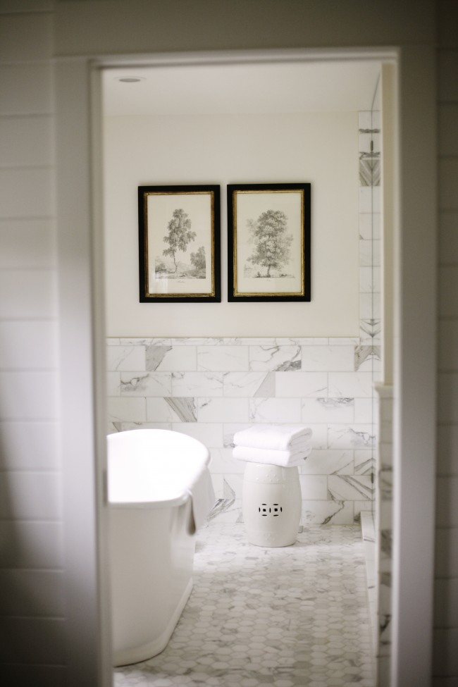 Designed by Katie Hackwork for H2 Design + Build. A marble octagon floor with  rectangular dimensional stone walls are complimentary. The addition of a white ceramic barrel stool and traditional prints on the wall are classic and refined.