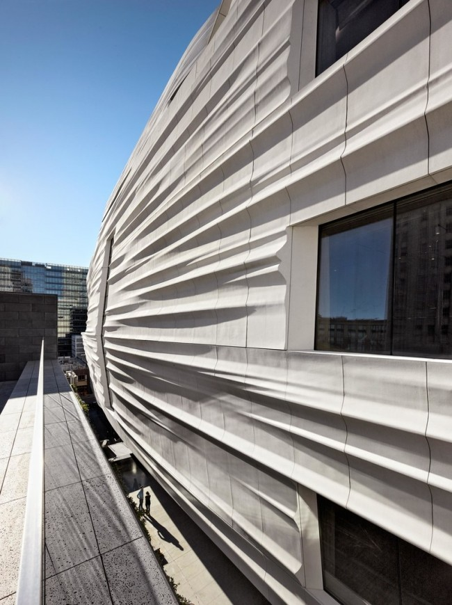 The exterior of the new building is clad in undulating panels of fiberglass-reinforced panels.