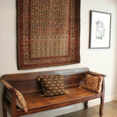 Inherited antique Caucasian Kuba (hanging) and Bokhara carpets shown to great effect against rustic antique Austrian settle, needleworked cushions and old Bokhara carpet. The soft patina on both textiles and period furniture create a warm and gentle aesthetic.