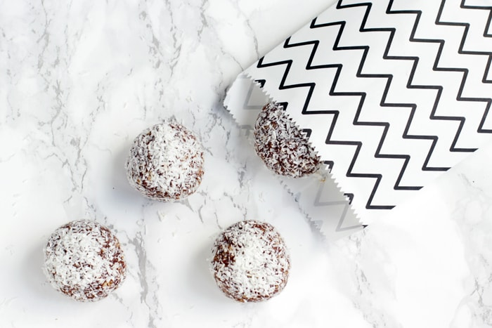 Swedish Chocolate Balls on marble board and in small white with black zig zag lines paper package