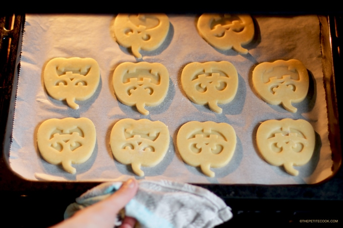 Hand putting the pumpkin shaped italian shortbread cookies on baking tray with parchment paper in the oven