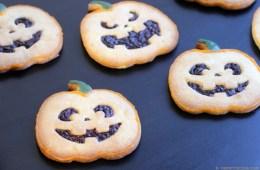 Pumpkin-shaped Halloween Italian Shortbread Cookies recipe on black background next to half pumpkin