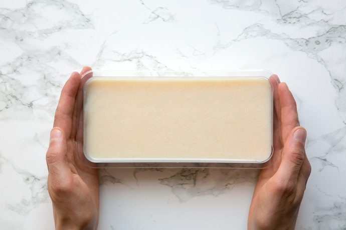 homemade butter with a2 milk into a plastic rectangular mould, held by hands