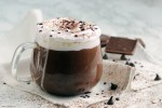 Italian Hot Chocolate in a clear glass on white napkin and chocolate in the background