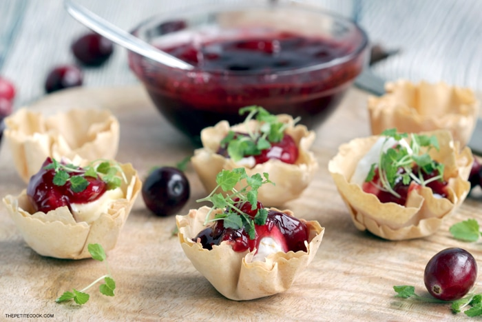 brie and cranberry cups on a wood board, homemade cranberry sauce in the background
