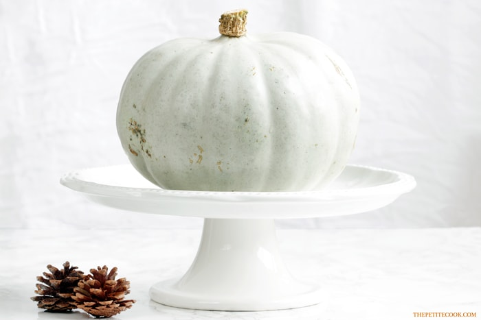 white pumpkin used for barley risotto with pumpkin on a white cake stand next to two pine cones