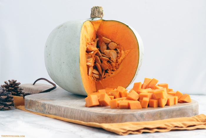 open pumpkin and cubes on wood board over orange napkin with two pine cones in the background