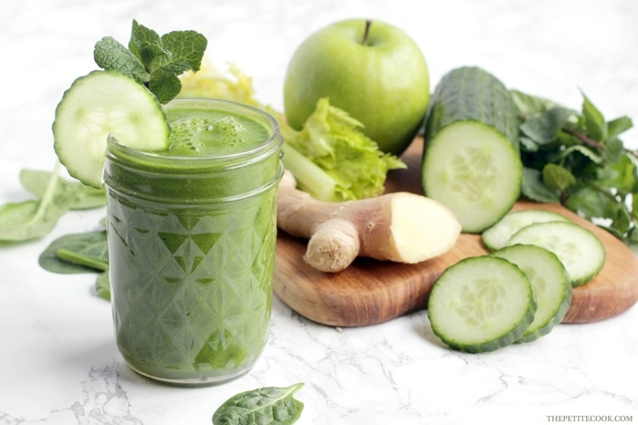 morning green juice in a glass, next to a wood board with fresh ginger, celery stalks, cucumber and cucumber slices, green apple and spinach leaves