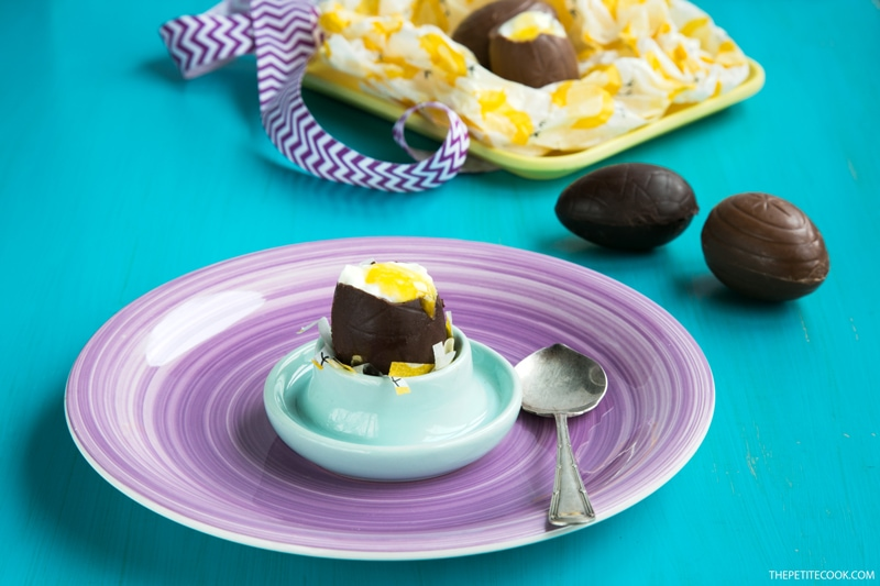 Cheesecake Chocolate Eggs on egg holder over a purple plate next to a spoon, more cheesecake eggs in the background
