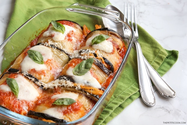Eggplant spaghetti sandwiches in baking dish next to green napkin and spoon and fork on top