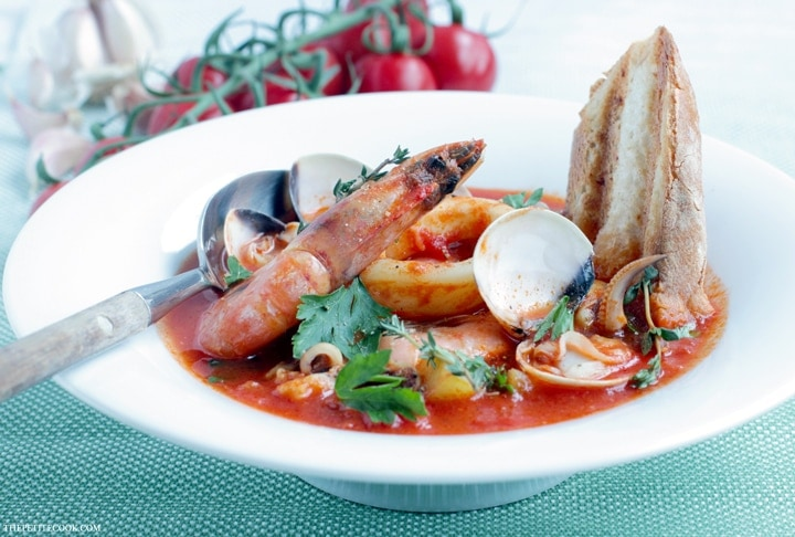 This simple Seafood Bouillabaisse is love at first spoon - Filled with aromatic Mediterranean flavors infused in a delicate saffron aroma. This light and easy version is ready in 30 mins and makes the most of seasonal ingredients for a simple and elegant heart-warming meal. Recipe from thepetitecook.com