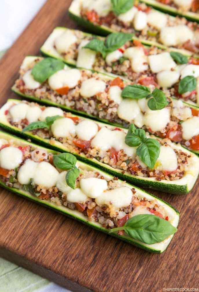 Zucchini boats stuffed qith quinoa and pico de gallo, topped with melted mozzarella cheese and basil leaves, on wood board with green napkin beneath
