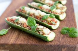 zucchini boats stuffed with quinoa and pico de gallo, topped with melted mozzarella cheese and basil leaves on a wood board