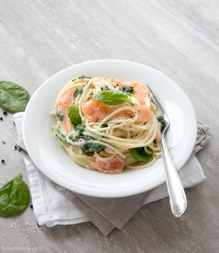 This Salmon and Spinach Spaghetti recipe has the most amazing and easy creamy sauce - Packed with nutrients, it comes together in just 15 min! Recipe from thepetitecook.com
