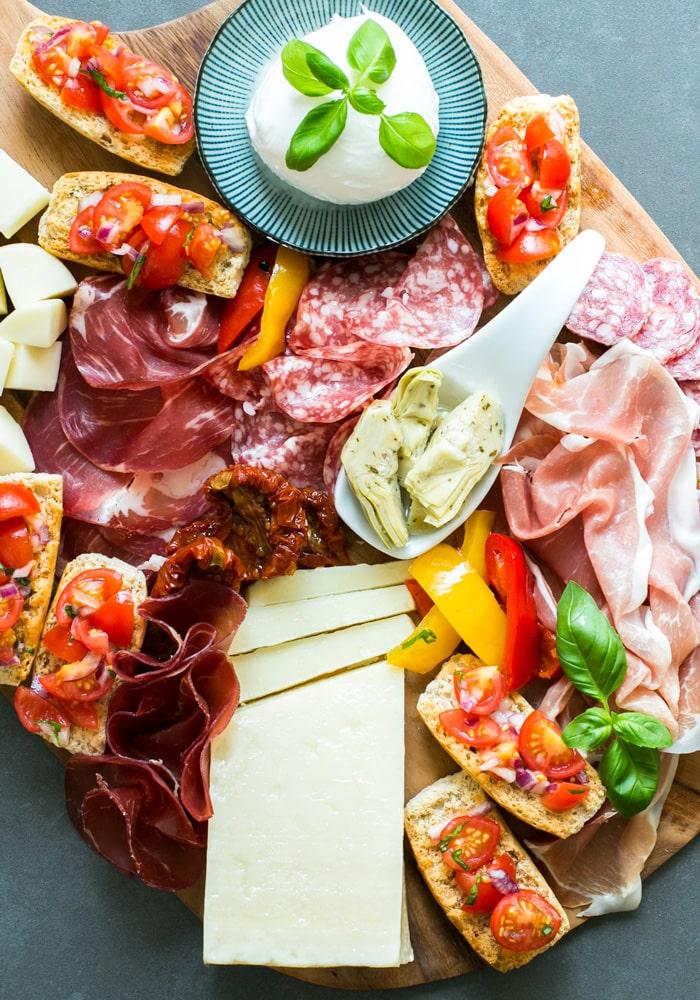 italian aperitivo platter with salami, cheese, bruschetta, mozzarella, ham, artichokes, bresaola and roasted peppers