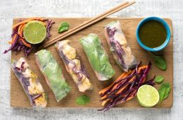 vietnamese summer rolls, chopsticks, halved lime, carrot sticks and sliced cabbage, small blue pot with cilantro dipping sauce on a wood board