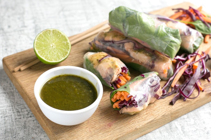 vietnamese summer rolls on a wood board with halved lime, chopsticks and a small white pot with cilantro dipping sauce.