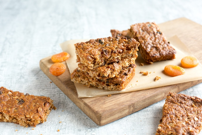 Vegan fruit flapjacks on a wood board covered with parchment paper, dried apricots on the left